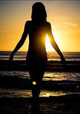 fotografia di una ragazza che esce dall'acqua con il sole che tramonta alle sue spalle